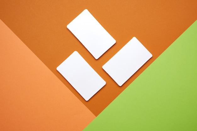 Mucchi dei biglietti da visita in bianco del libro bianco su fondo verde arancio