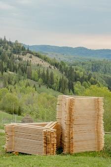 Mucchi dei bordi di legno su erba verde con le montagne, tavolato per costruzione. pila di legname di legno di materiale da costruzione degli spazii in bianco di legno
