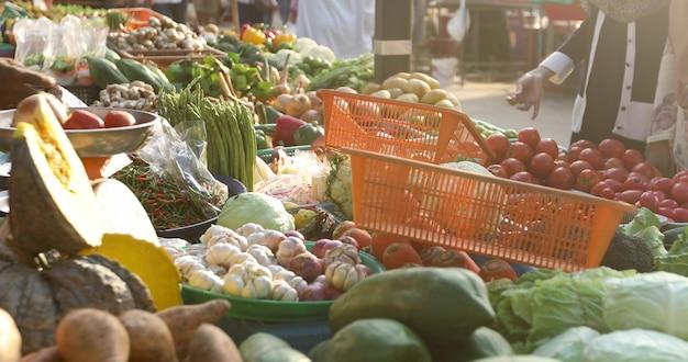 Mucchi delle verdure fresche mature e della frutta esotica disposte sulla stalla il giorno soleggiato sul mercato di strada