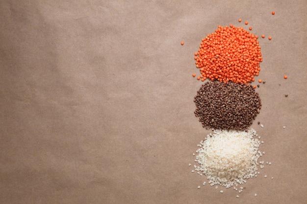 Mucchi di lenticchie, buckwheet, riso sullo sfondo marrone con copyspace