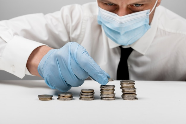 Mucchi di monete e uomo che indossa una maschera medica