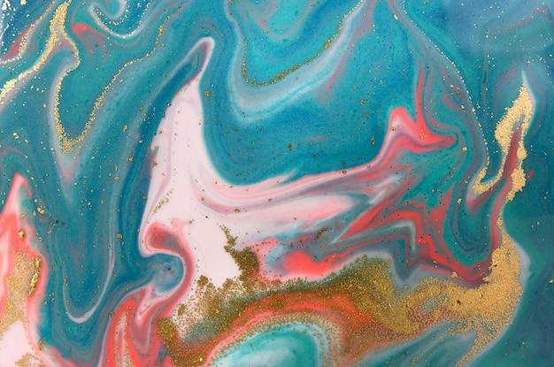 Mucchi di paillettes dorate su macchie di vernice rosa e blu.