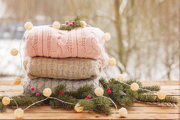 Mucchio accogliente dei maglioni tricottati sulla tavola di legno sulla natura di inverno.
