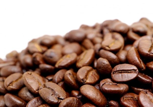 Mucchio alto chiuso dei chicchi di caffè arrostiti isolati su fondo bianco