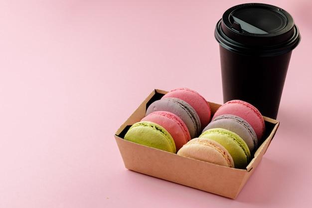 Mucchio dei biscotti variopinti del maccherone su fondo rosa