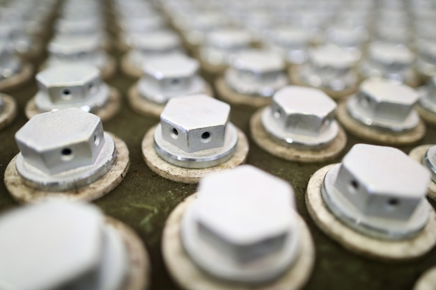 Mucchio dei bulloni in scatola speciale nell'impianto industriale