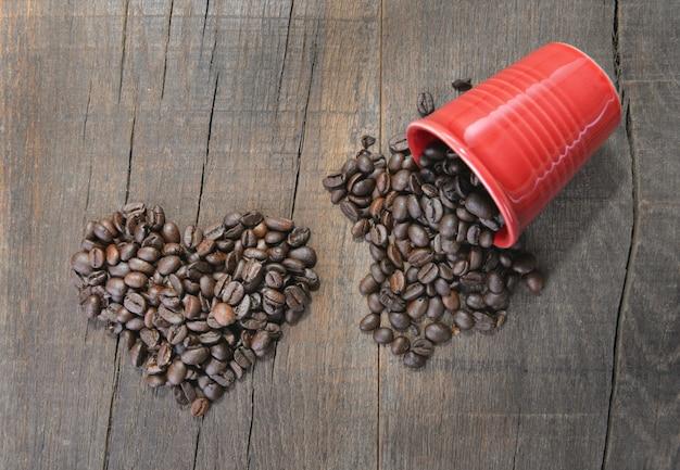 Mucchio dei chicchi di caffè che formano un cuore accanto ad una tazza rossa rovesciata su fondo di legno rustico