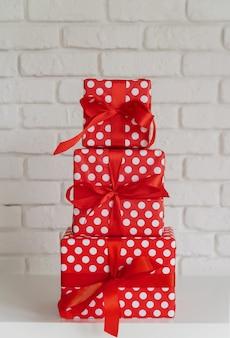 Mucchio dei contenitori di regalo rossi sulla parete bianca