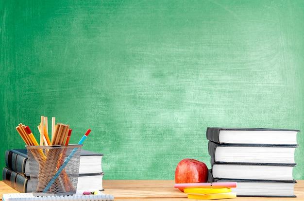 Mucchio dei libri con il contenitore di merce nel carrello della carta e della penna, della mela e delle matite sulla tavola di legno