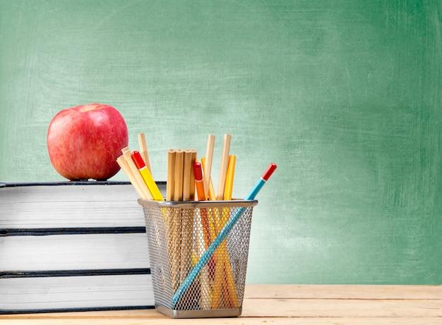 Mucchio dei libri con il contenitore di merce nel carrello delle matite e della mela sulla tavola di legno con la lavagna