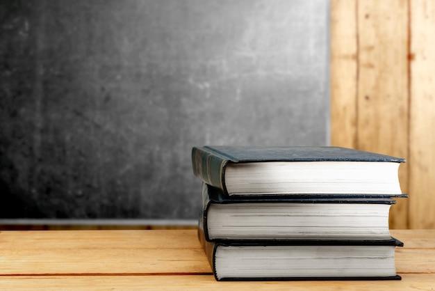 Mucchio dei libri sulla tavola di legno con la lavagna