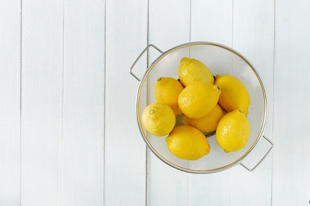 Mucchio dei limoni in colapasta su una tavola di legno con la vista superiore dello spazio della copia