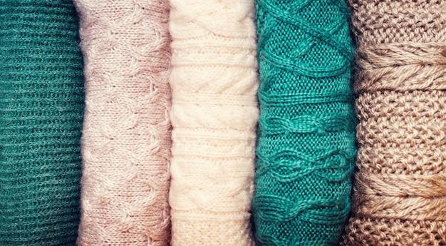 Mucchio dei maglioni lavorati a maglia della lana su priorità bassa bianca con lo spazio della copia. maglieria, vestiti