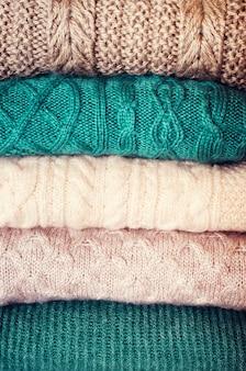 Mucchio dei maglioni lavorati a maglia della lana su priorità bassa bianca con lo spazio della copia.