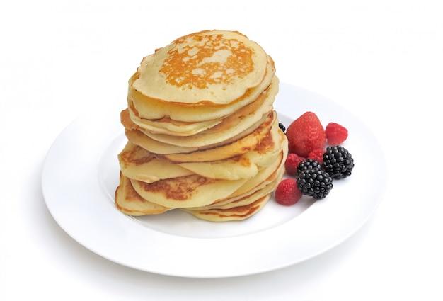 Mucchio dei pancake casalinghi freschi su un piatto con alcune bacche su fondo bianco