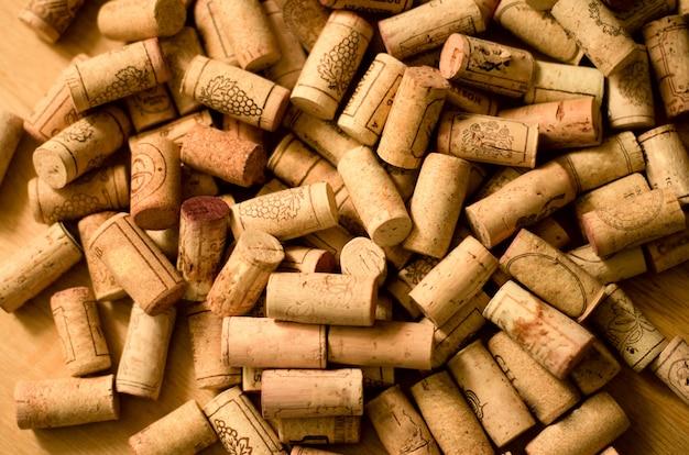 Mucchio dei sugheri del vino su fondo di legno