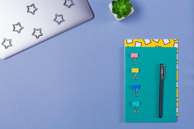 Mucchio dei taccuini, del computer portatile e dello stazionario luminosi sulla scrivania blu. copia spazio. spazio libero.