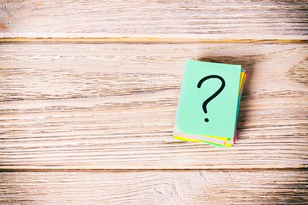 Mucchio della carta del punto interrogativo sul concetto della tavola per la vista superiore di confusione con lo spazio della copia tonificato