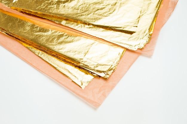 Mucchio della foglia di oro quadrata su bianco