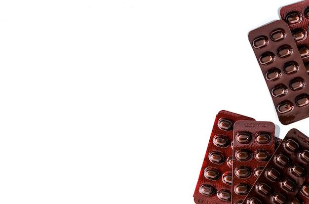 Mucchio della medicina delle pillole delle compresse nel blister resistente alla luce su fondo bianco. pillole di compresse di vitamine e minerali per donne in gravidanza. pillole di compresse per il trattamento dell'anemia fumarata ferrosa.