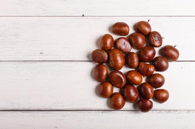Mucchio delle castagne dolci su fondo di legno bianco