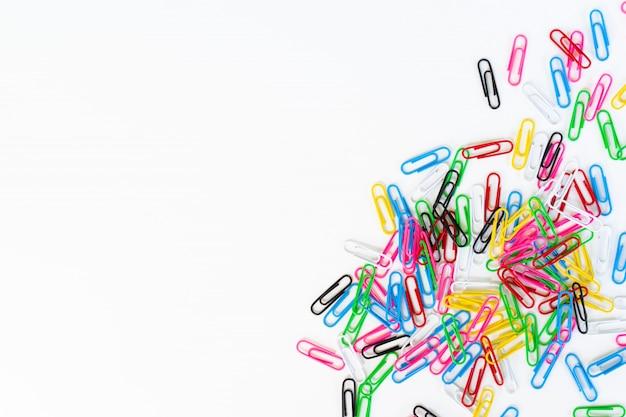 Mucchio delle clip di carta colorate isolate su un bianco