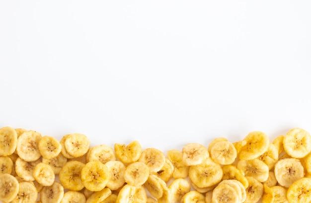 Mucchio delle fette secche della banana con lo spazio della copia isolato su bianco