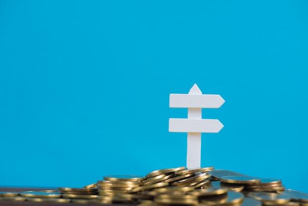 Mucchio delle monete dorate e del segno bianco del bordo di legno
