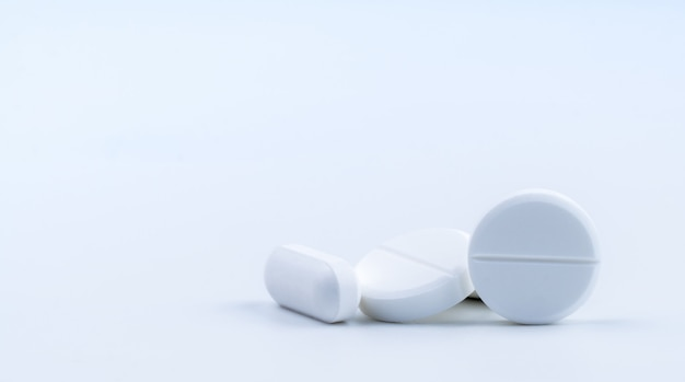 Mucchio delle pillole bianche della compressa di forma rotonda e oblunga isolate