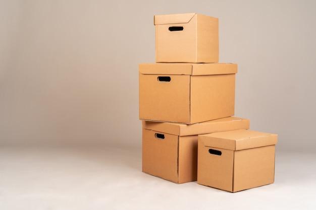 Mucchio delle scatole marroni su fondo grigio