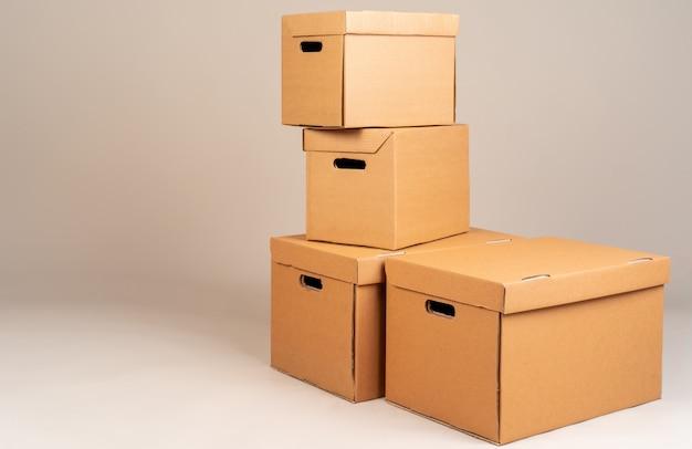 Mucchio delle scatole moxing marroni su fondo grigio