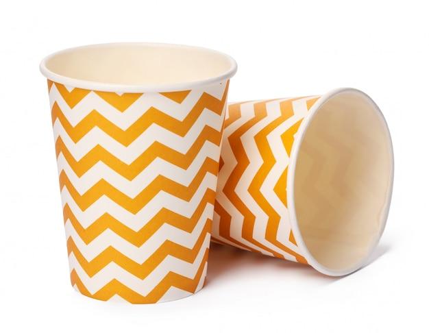Mucchio delle tazze di cartone con il modello geometrico beige isolato su fondo bianco