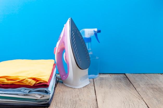 Mucchio di abiti colorati e ferri da stiro, bottiglie spray, sulla tavola di legno, sfondo di colore blu