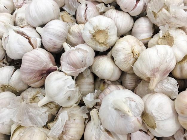 Mucchio di aglio bianco trama. aglio fresco sulla foto del primo piano della tavola del mercato. immagine di spezie cibo sano vitamina.