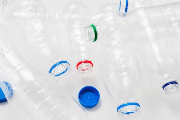 Mucchio di bottiglie di plastica e tappi su sfondo grigio