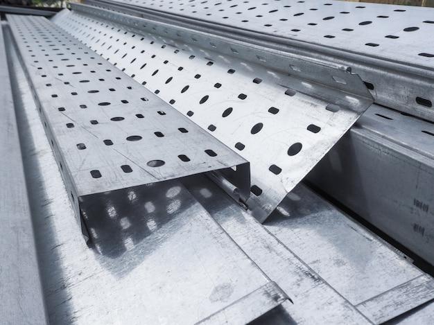 Mucchio di canali in acciaio per la costruzione di una casa in un sito all'aperto. travi in acciaio per il tetto. tubi profilati