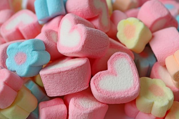 Mucchio di caramelle marshmallow a forma di fiore rosa e bianco a forma di cuore e colore pastello