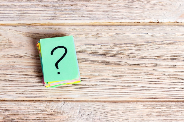Mucchio di carta del punto interrogativo sul concetto di tavolo per confusione