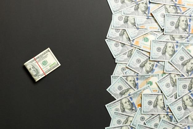 Mucchio di cento banconote in dollari su sfondo colorato