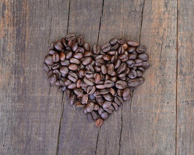 Mucchio di chicchi di caffè che formano un cuore su un fondo di legno rustico