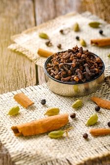 Mucchio di chiodi di garofano secchi in ciotola, sul tavolo di legno