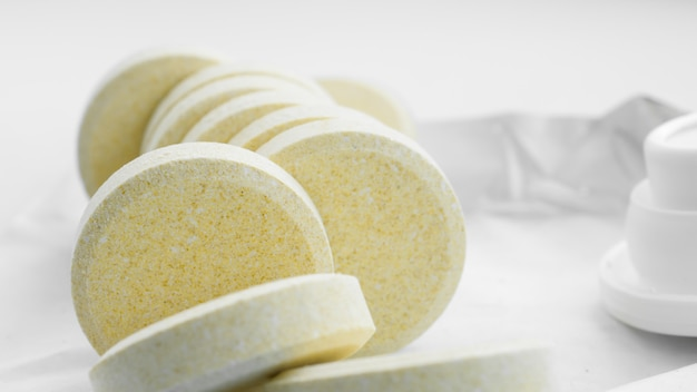 Mucchio di compresse di vitamine effervescenti solubili su uno sfondo di carta. vitamine e integratori alimentari. assistenza sanitaria e medica. vista frontale.