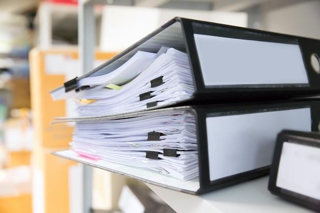 Mucchio di documenti con clip nere in cartelle si accumulano.