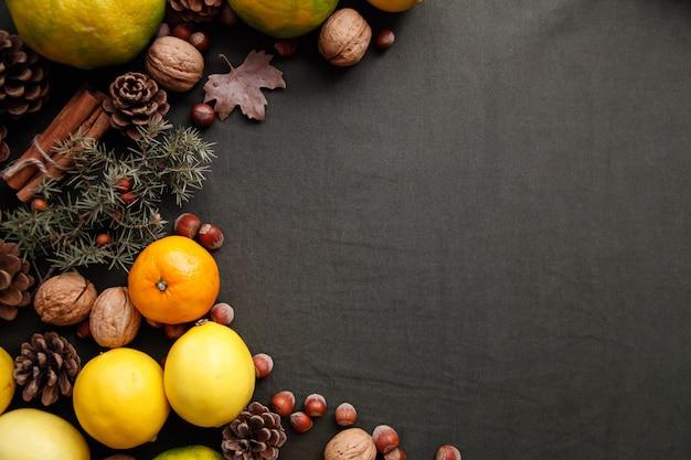 Mucchio di frutta fresca, coni e noci sul tessuto verde scuro. sfondo del ringraziamento con copyspace
