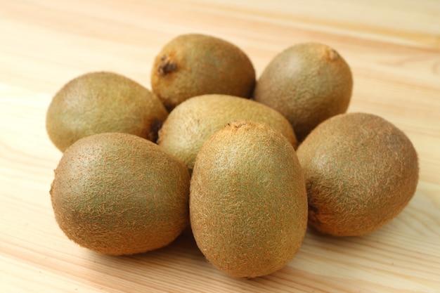 Mucchio di interi frutti del kiwi maturo fresco sulla tavola di legno