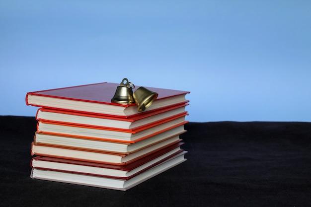 Mucchio di libri e mela in alto su sfondo blu