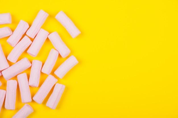 Mucchio di marshmallow rosa su uno sfondo giallo