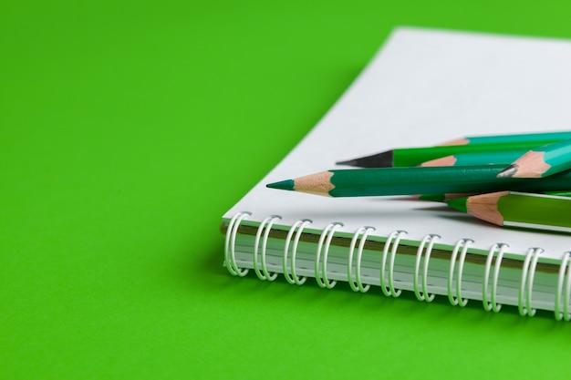 Mucchio di matite su uno sfondo verde brillante