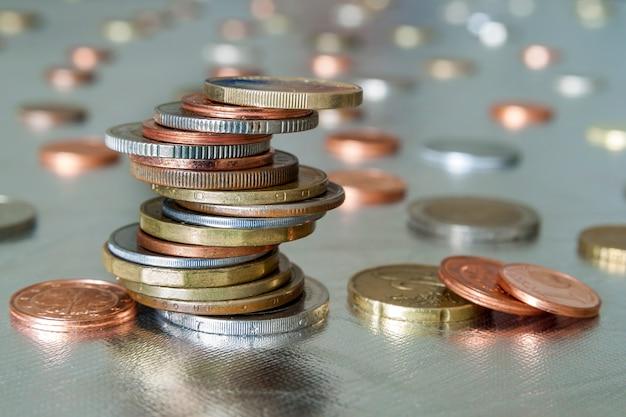 Mucchio di monete lucenti di diverse dimensioni e colori impilati in modo non uniforme l'uno sull'altro. risparmio di denaro e concetto di rischio finanziario.