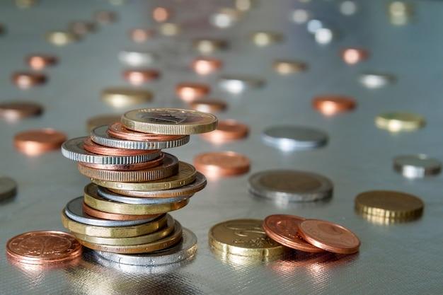 Mucchio di monete lucide diverse dimensioni e colori impilati in modo non uniforme l'uno sull'altro su sfondo astratto blu sfocato colorato. risparmio di denaro e concetto di rischio finanziario.